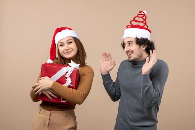 Conceito de clima festivo de ano novo com um casal adorável e engraçado usando chapéu de papai noel vermelho na filmagem cinza