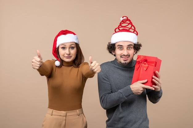 Conceito de clima festivo de ano novo com um casal adorável e feliz usando chapéus vermelhos de papai noel na filmagem cinza
