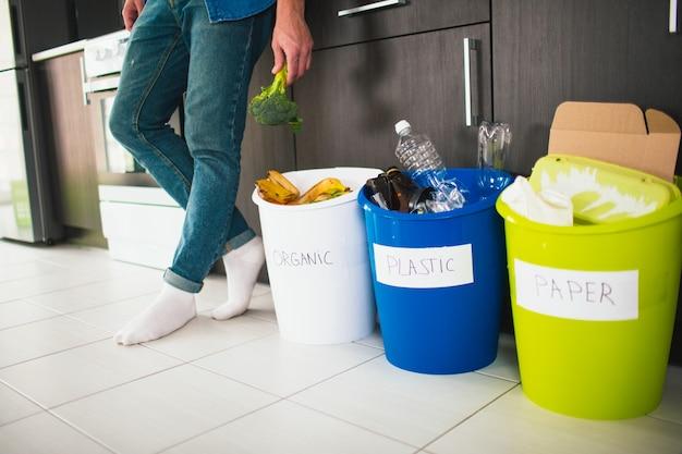 Conceito de close-up. classifique o lixo em casa. existem três baldes para diferentes tipos de lixo. cara classifica resíduos na cozinha