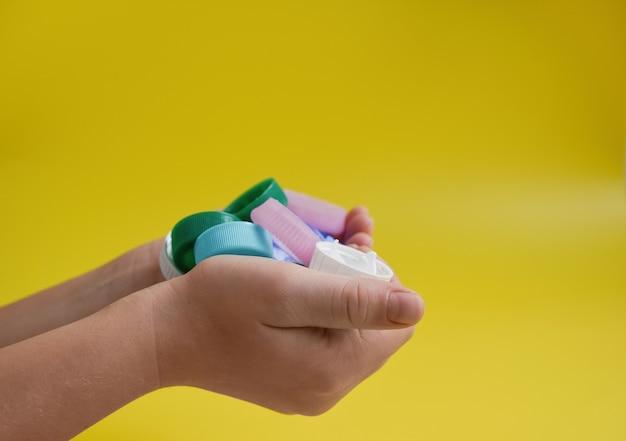 Conceito de coleta de reciclagem de poluição de plástico tampas de plástico nas mãos de uma criança