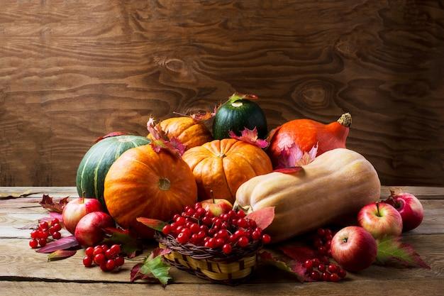 Conceito de colheita abundante com abóboras, maçãs, bagas e folhas de outono