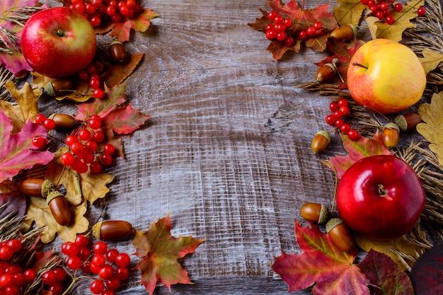 Conceito de colheita abundante com maçãs, bolotas, bagas e folhas de outono