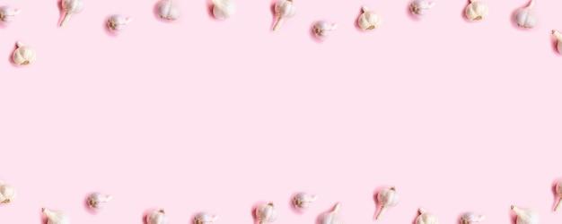 Conceito de colheita. bulbos de quadro de alho em um fundo rosa de madeira