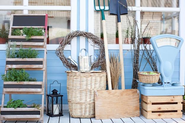 Conceito de colheita. cestas de vime ao lado de equipamento de jardim junto à parede de uma casa de campo azul. a decoração do pátio de uma casa de campo. conceito de jardinagem. outono colheita da abundância.