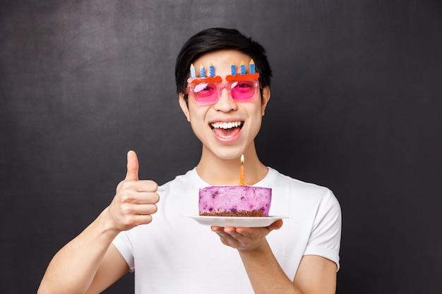 Conceito de comemoração, feriado e aniversário. o retrato do close-up do cara feliz aniversário animado em copos de festa engraçada, mostra o polegar e segura o bolo delicioso, fazendo desejos na vela acesa