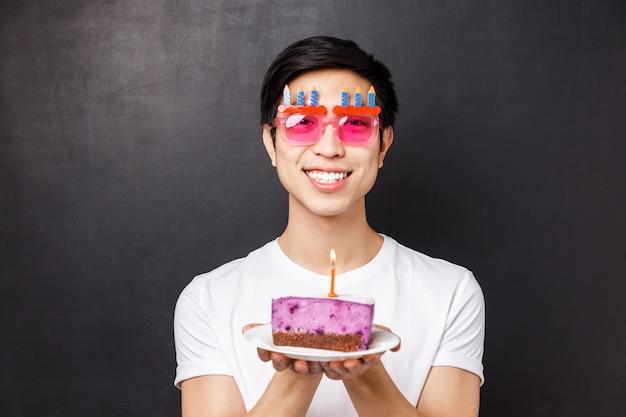 Conceito de comemoração, feriado e aniversário. retrato de close-up de animado e feliz, alegre homem asiático comemorando o dia b em óculos engraçados, segurando o bolo, vela de sopro,