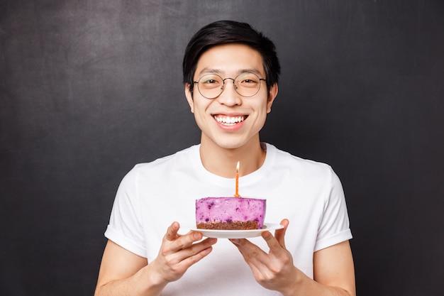 Conceito de comemoração, feriado e aniversário. retrato de close-up de feliz, alegre dia b cara segurando o bolo com uma vela acesa, sorrindo otimista, pensando o que desejo fazer e explodir,
