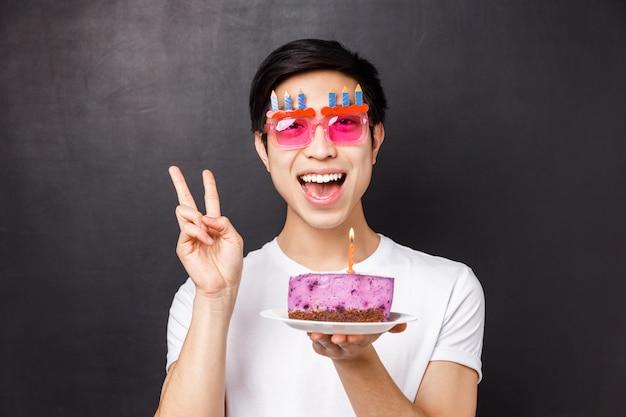 Conceito de comemoração, feriado e aniversário. retrato do close-up de alegre homem asiático engraçado se divertindo, aproveitando a festa de b-dia, mostrar sinal de paz sorrindo e segure o bolo com vela acesa, faça o desejo