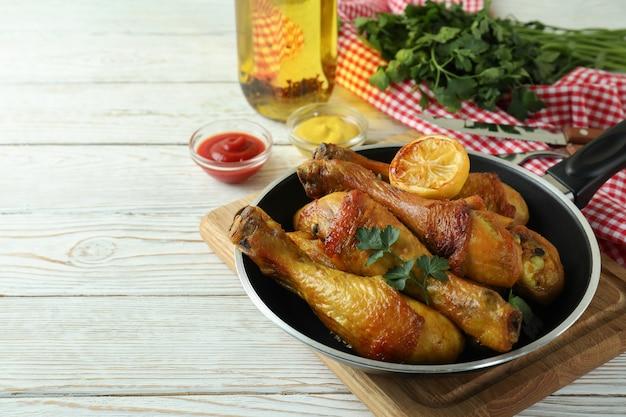 Conceito de comer deliciosa com panela de coxinhas de frango assado na mesa de madeira branca