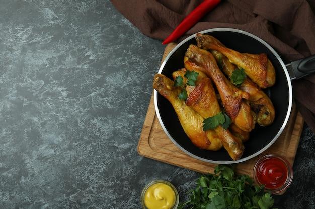 Conceito de comer deliciosamente com uma panela de coxinhas de frango assado na mesa esfumada preta