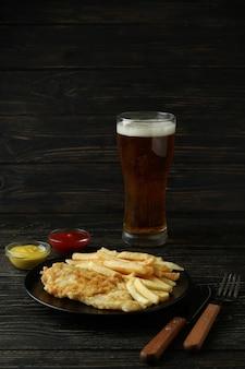 Conceito de comer saboroso com batatas fritas e peixe e cerveja na madeira