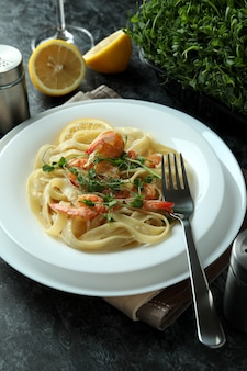Conceito de comer saboroso com macarrão de camarão na mesa esfumada preta