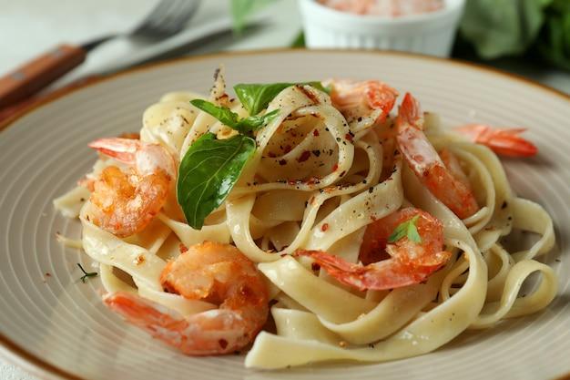 Conceito de comer saboroso com macarrão de camarão na mesa texturizada branca