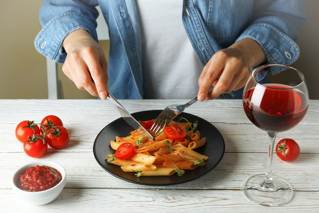 Conceito de comer saboroso com mulher come macarrão com molho de tomate na mesa de madeira branca