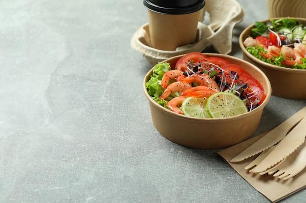 Conceito de comer saboroso com saladas de camarão na mesa cinza