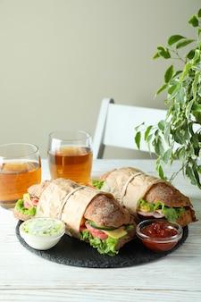 Conceito de comer saboroso com sanduíches de ciabatta na mesa de madeira branca