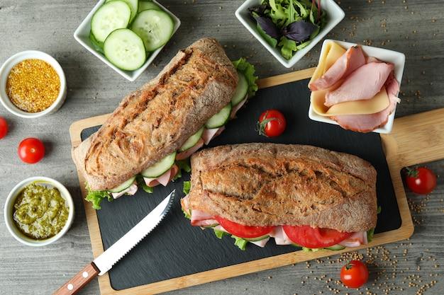 Conceito de comer saboroso com sanduíches de ciabatta na mesa texturizada cinza