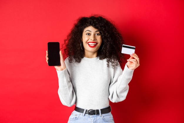 Conceito de comércio eletrônico e compras online. mulher alegre, sorrindo, mostrando o cartão de crédito de plástico e a tela vazia do smartphone, de pé sobre um fundo vermelho.