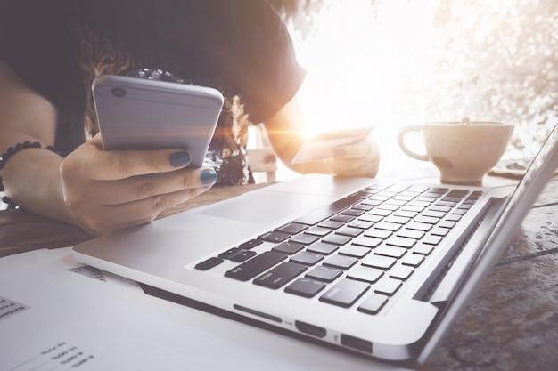 Conceito de comércio eletrônico. mulher que usa o portátil e o cartão de crédito para a compra em linha na cafetaria.