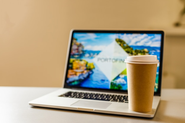 Conceito de comércio eletrônico: viagens on-line, xícara de café de papel artesanal perto do laptop