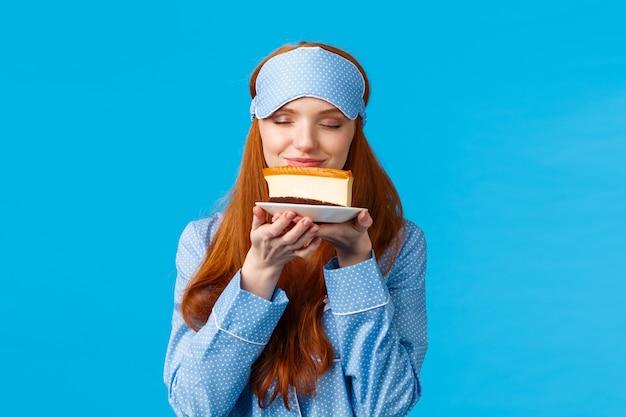 Conceito de comida, alimentação e sobremesas. mulher ruiva bonita alegre em roupa de dormir, máscara de dormir, fechar os olhos cheirando saborosa fatia de bolo quer comer doces, mas na dieta, em pé fundo azul