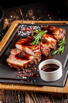 Conceito de comida americana. costelinha de porco grelhada com molho grelhado, com fumo, especiarias e alecrim. imagem de fundo. copie o espaço