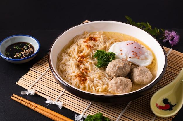 Conceito de comida asiática macarrão de ovo ramen estilo asiático com almôndega no fundo preto fosco de bambu com espaço de cópia