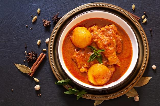 Conceito de comida asiática picante caseiro masala de frango ou curry massaman tailandês com especiarias em primeiro plano em pedra de ardósia preta com espaço de cópia