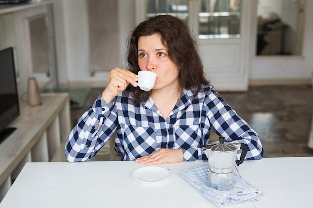 Conceito de comida, bebida e pessoas. mulher jovem e bonita na cafeteria bebe café.