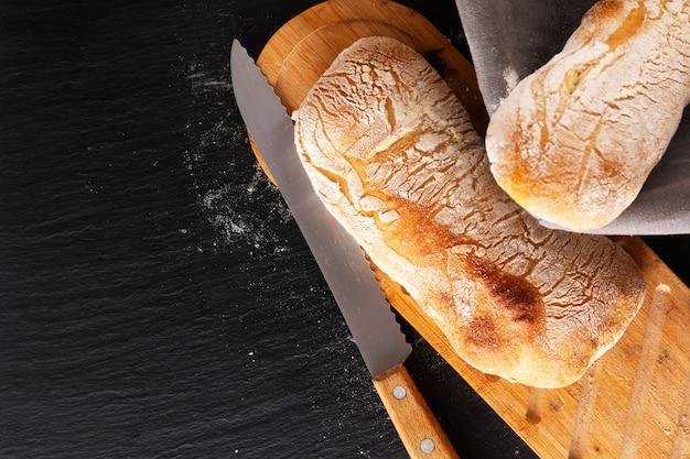 Conceito de comida caseira artesanal estilo italiano clássico massa fermento pão ciabatta na placa de ardósia preta com espaço de cópia