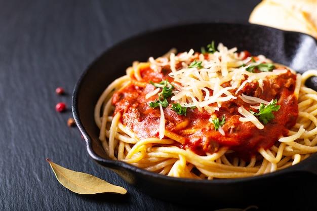 Conceito de comida caseira espaguete à bolonhesa em ferro fundido