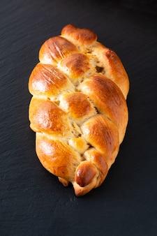 Conceito de comida caseira fresco cozido pão trança chalá massa em pedra ardósia preta