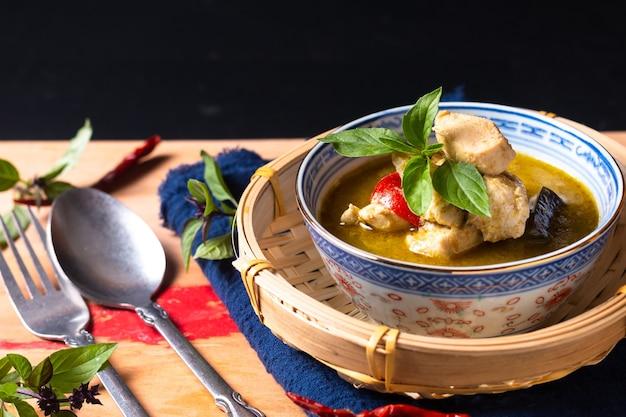 Conceito de comida caseiro tailandês frango curry verde na placa de madeira com espaço de cópia