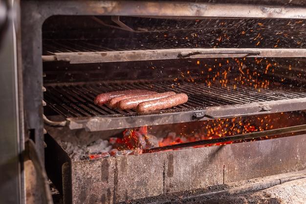 Conceito de comida, comida deliciosa e pratos de carne - salsichas de cavalo preparadas no churrasco.