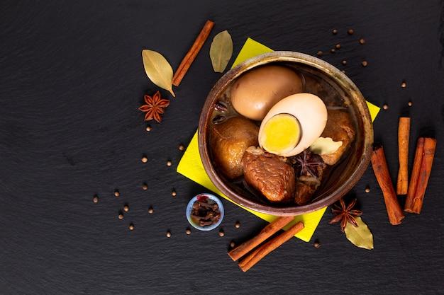 Conceito de comida cozinha tailandesa barriga de porco e ovo com cinco especiarias ensopado perfumado moo palo na ardósia preta
