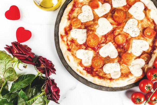 Conceito de comida de dia dos namorados, margarita pizza com queijo em forma de coração, vista superior de cena de mármore branco, com rosas