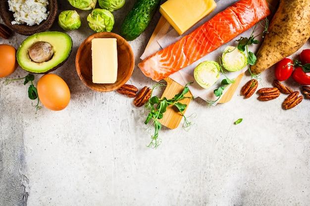 Conceito de comida de dieta equilibrada. peixe, ovos, queijo, nozes, manteiga e legumes