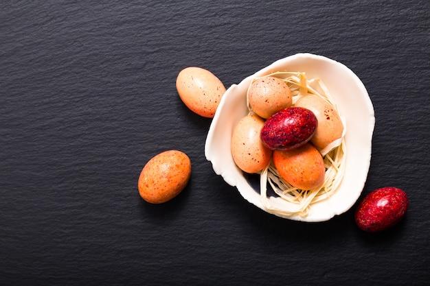 Conceito de comida de férias doces coloridos e ovos de páscoa de chocolate na placa de ardósia preta