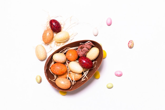 Conceito de comida de férias doces coloridos e ovos de páscoa de chocolate no fundo branco