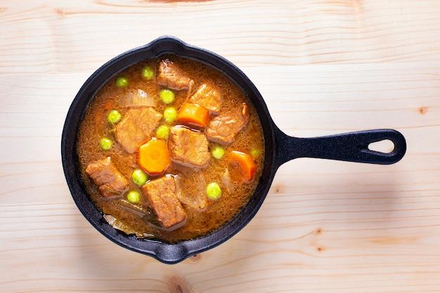 Conceito de comida de inverno caseiro ensopado orgânico ou bourguignon em frigideira de ferro fundido