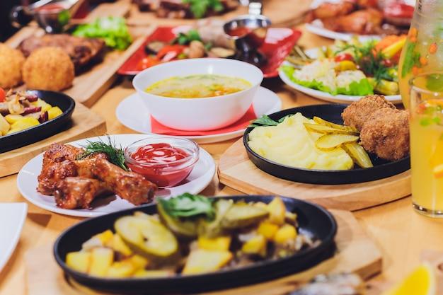 Conceito de comida de jantar. mesa de jantar com salsicha grelhada, envoltórios de tortilla, bebida de cerveja e pratos diferentes na mesa de madeira, estilo rústico.