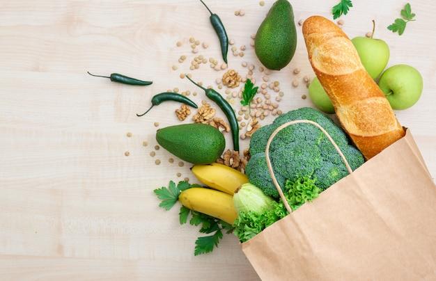 Conceito de comida de saco. compras compras saco de papel com alimentos saudáveis em uma vista superior de madeira