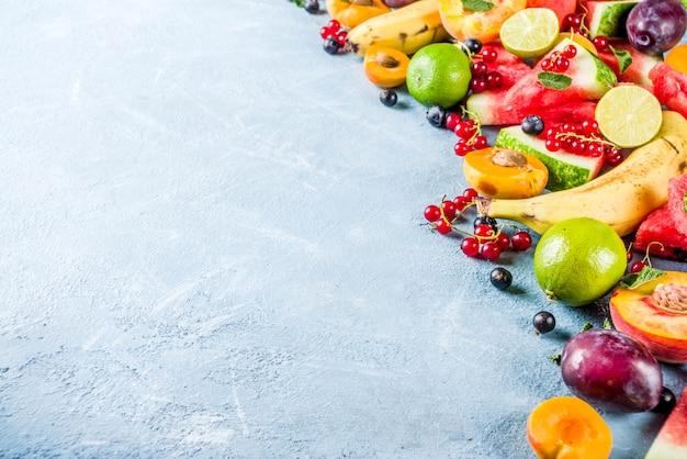 Conceito de comida de verão vitamina, várias frutas e bagas melancia pêssego hortelã ameixa damascos groselha mirtilo, criativo plano leigos sobre fundo azul claro