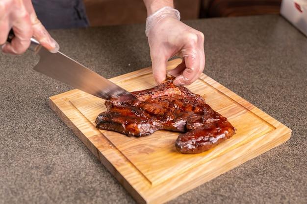 Conceito de comida, deliciosa e artesanal - homem que corta bife de cavalo.