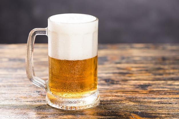 Conceito de comida e bebida - cerveja de vidro em fundo de madeira com espaço de cópia.