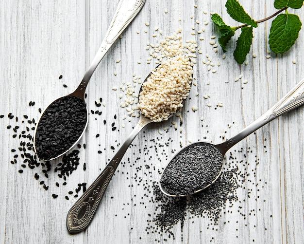Conceito de comida e bebida saudável. sementes de gergelim preto e branco e sementes de papoula em uma colher em uma mesa de madeira