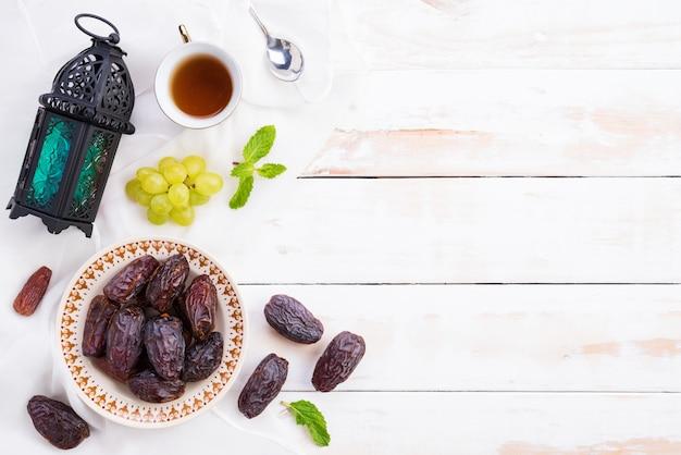 Conceito de comida e bebidas de ramadã. lanterna de ramadã com chá, fruta de datas, flat leigos.