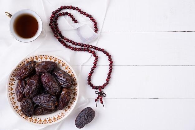 Conceito de comida e bebidas de ramadã. rosário de madeira, chá e fruta das datas