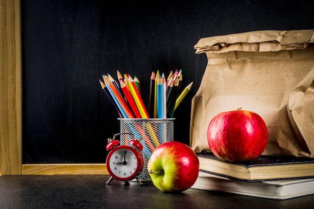 Conceito de comida escolar saudável, saco de papel com almoço, maçã, sanduíche, livros e despertador na lousa
