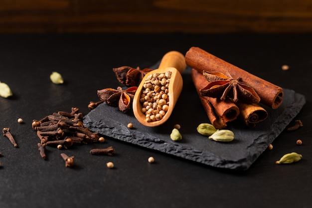 Conceito de comida exótica ervas mistura das especiarias orgânicas em uma placa de pedra ardósia preta com cópia